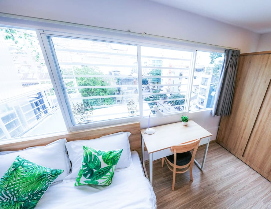 rooftop bedroom with large windows providing city view