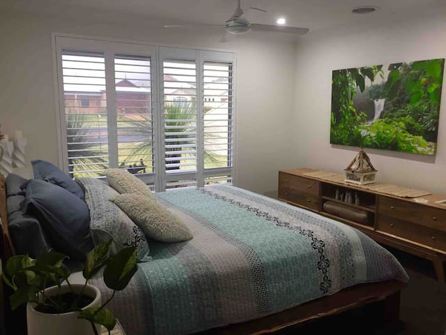 The main bedroom is a very comfortable King size bed including linen and towels . The room has a ceiling fan , walk in robe and en-suite bathroom and toilet and is located at the front of the home .
