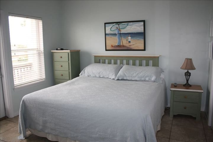 This king-size mattress is new and super comfortable. There is a patio outside this bedroom.
