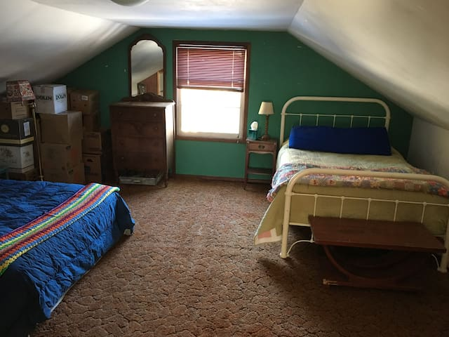 Attic bedroom has two double beds, two dressers and a desk