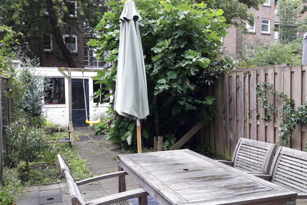 Sunny garden includes gardenfurniture, parasol and swing.