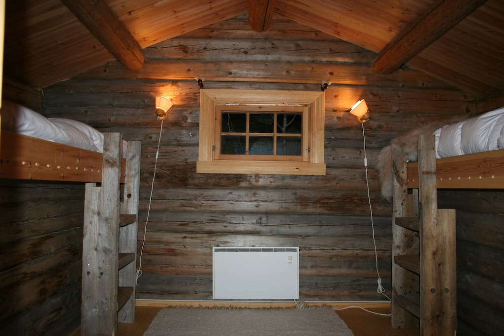 The cabin is made with logs, the way food storage houses were made before, but now with beds and heating. Please note that from May the bed on the right will be 120 cm wide, thus extending to the edge of the window. Photo taken April 14,  2016.