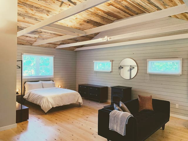Expansive master bedroom with lofted reclaimed wood ceilings, views from every window and a cozy private sitting area with fireplace