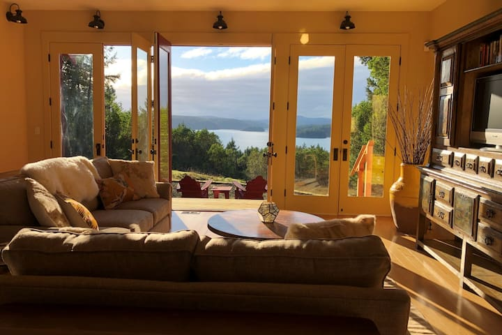 Living room walks out onto the back patio with a view of Westsound and San Juan Island.