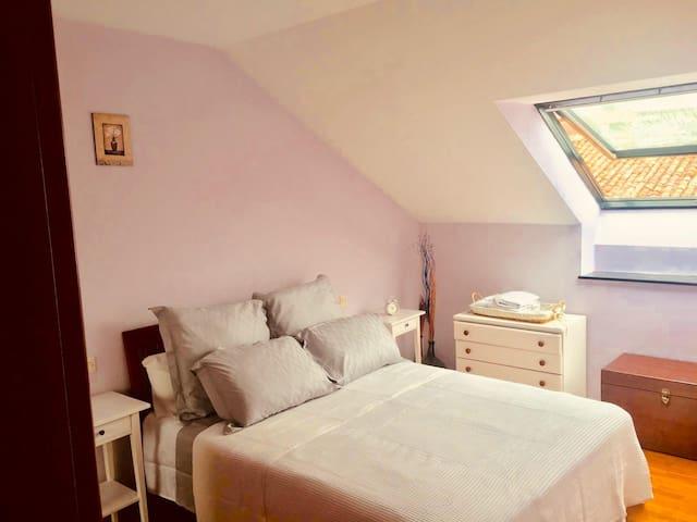 Habitación cama matrimonial con armario grande, mesitas, cómoda y baúl. A la izquierda de la ventana se ve la sierra del Cuera. A la derecha, se siente el mar.