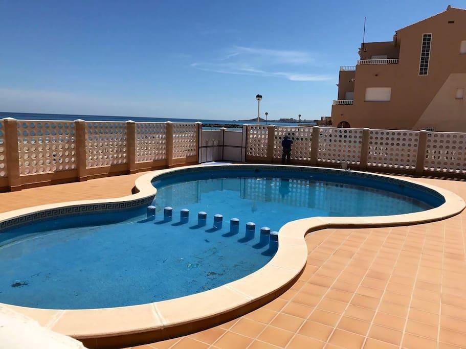 El apartamento cuenta con piscina comunitaria en primera línea de playa, ideal para quitarse la sal y la arena antes de volver a casa