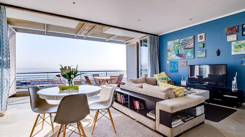 The spacious living and dining room boasts panoramic views of the new promenade, ocean and the city.