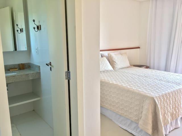 Suíte 1 (2ª andar). Com ar condicionado, Smart TV, Mesinhas de cabeceira, armário com cabideiro e gavetas, Pendurador de roupas, varanda com rede.