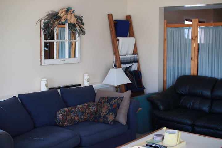 Blanket ladder, mirror and couches in living room.