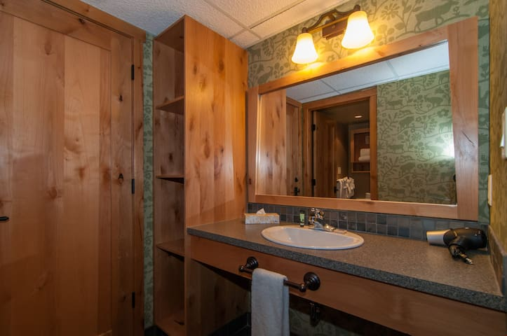 The spacious bathroom features lovely wooden touches along with a shower-tub combination.