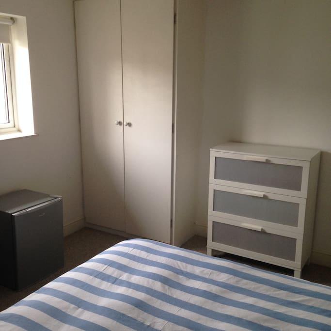 wardrobe, chest of drawers + fridge in room