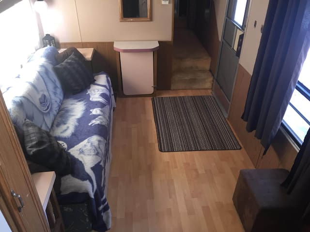 Large living area for the family to gather on those rainy days! Couch folds down to make a comfortable double size bed and there is enough floor space to add a queen size air mattress to accommodate 8 people in this camper in total .