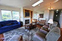 Living room with spectacular 180 degree ocean views, cable TV/DVD, gas fireplace, hide-a-bed couch and five arm chairs.