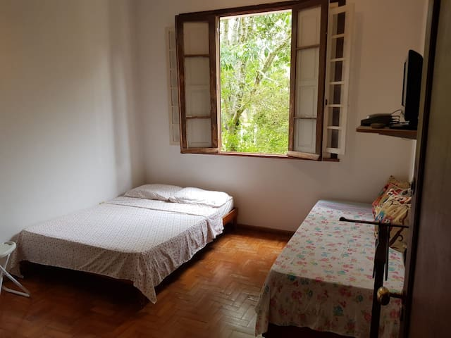 Vista da porta de entrada da suíte. Há duas camas, sendo uma de casal, e uma de solteiro.