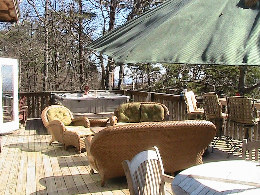 The large deck adds additional living space with seating, table, grill, and hot tub.