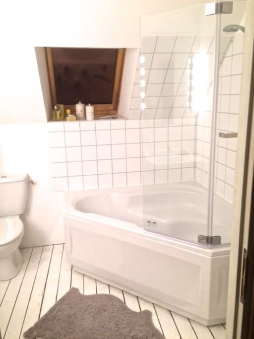 Brightly lit all-in-white bathroom with spacious corner bath and shower over