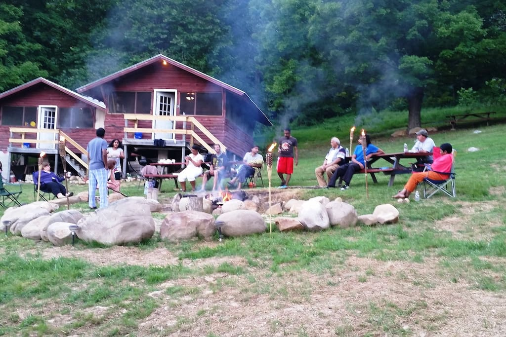 a big group enjoying the communal fire outside of the kitchen cabin