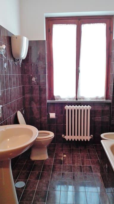 Bagno con vasca sulla destra, lavandino, bidet, termosifone e ampia finestra. Anche se non si vede dalla foto, sopra al lavandino c'è anche uno specchio.
