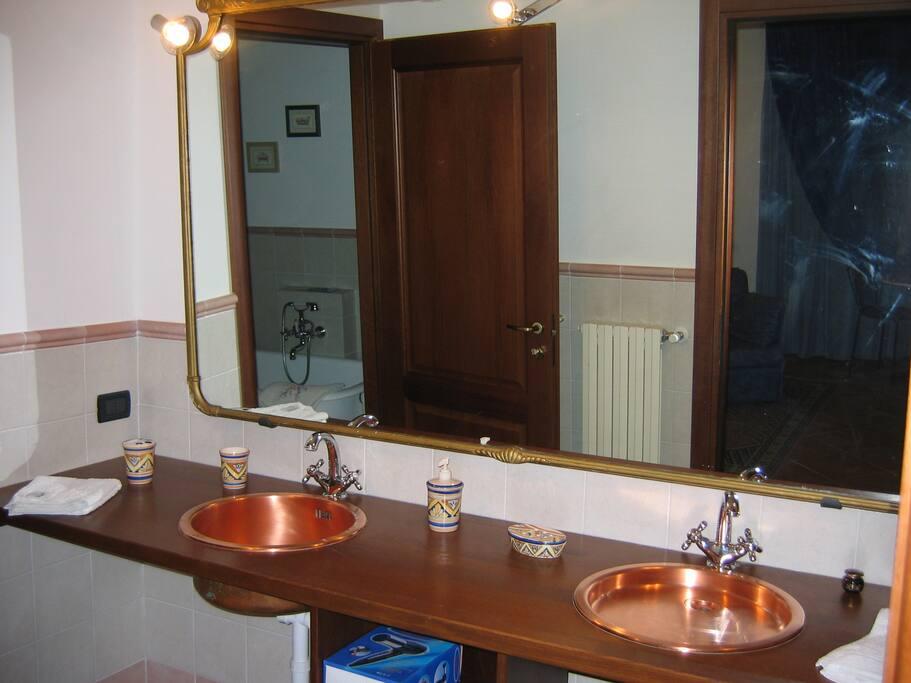 Bagno della junior suite con doppio lavabo in rame e servizio di cortesia completo