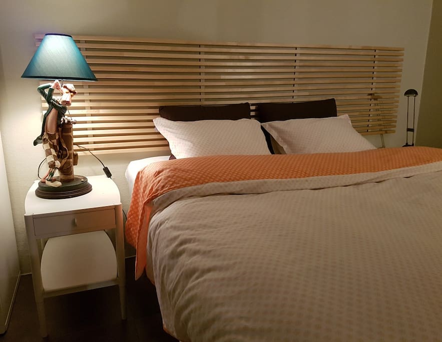 The comfortable double, queen sized bed is flanked by bed-side tables