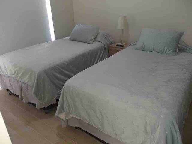 Pieza con dos camas y tele