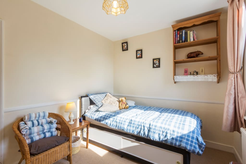 Our comfortable single bed, towels, chair & bookcase.
