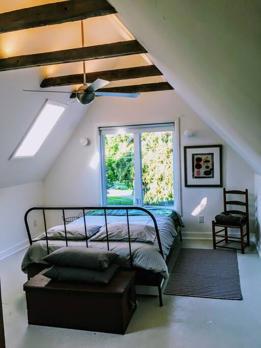 Upstairs bedroom with vaulted ceiling,  skylights and a large picture window overlooking the trees.
