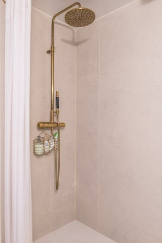 White tiled bathroom with brass details