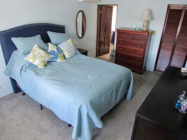 Master bedroom with queen size bed, AC, plenty of storage space and black out curtains for sleeping.
