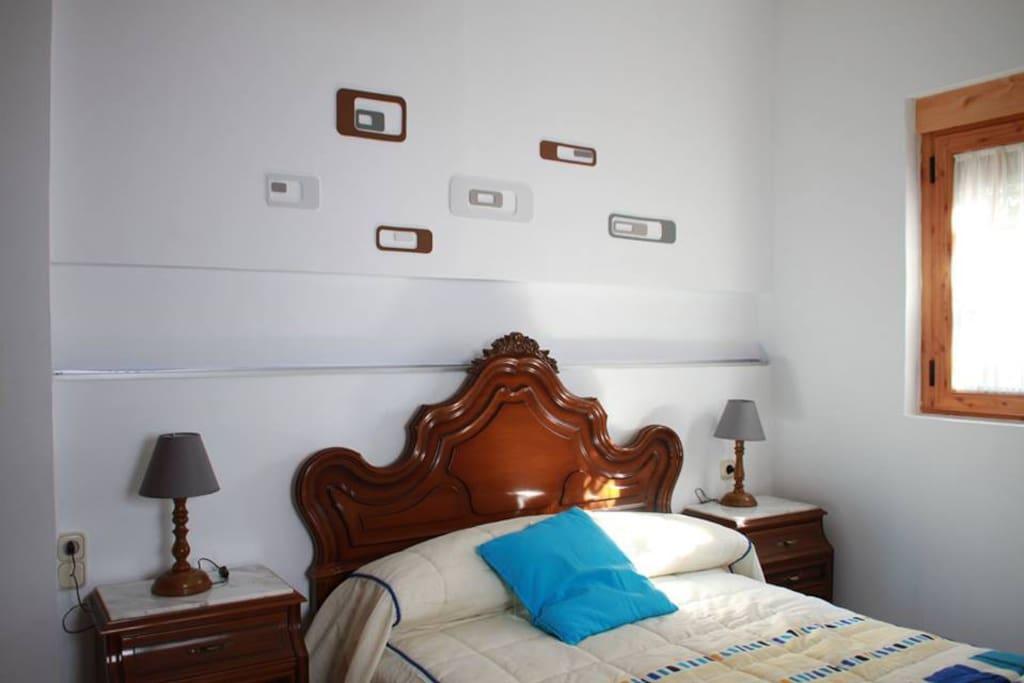 Dormitorio principal, mesitas de noche, armario. Con vistas a la calle, al patio de la casa y zona verde.