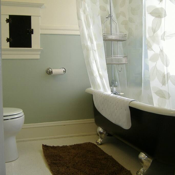 private bathroom with clawfoot soaking tub and shower