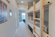 Custom twin bunk beds in upper hallway with Tuft & Needle memory foam mattresses