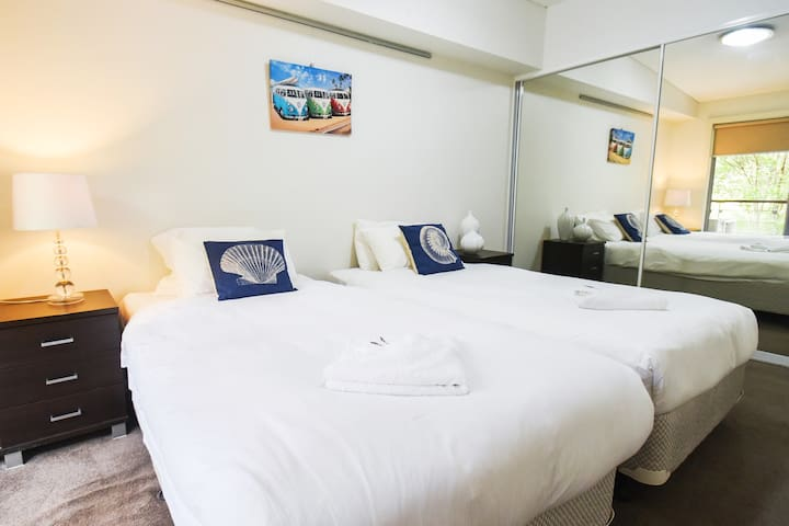 The second bedroom comes with 2 King Single beds, a wardrobe with a full-mirror slide door, and a small balcony.