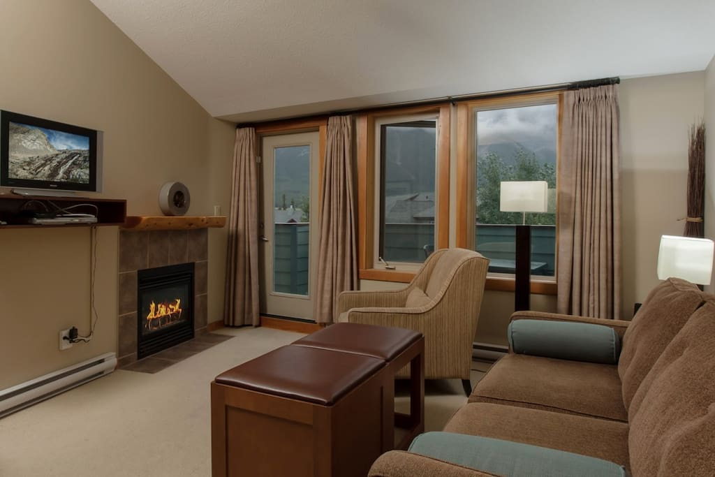 Featuring stylish furnishings around the stone-framed fireplace and TV