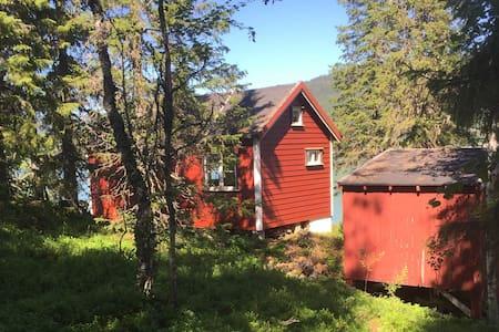 Sjarmerende hytte i vakre omgivelser ved vann.