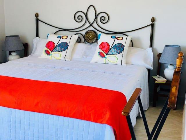 Dormitorio principal con cama extra grande y balconada con bonitas vistas al mar.