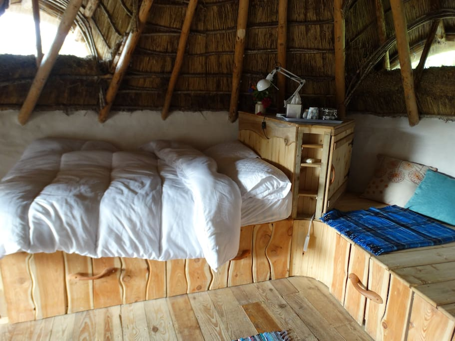 the soft comfortable double bed has a warm douvert and a reading light above. You sleep peacefully beneath a magical thatch roof