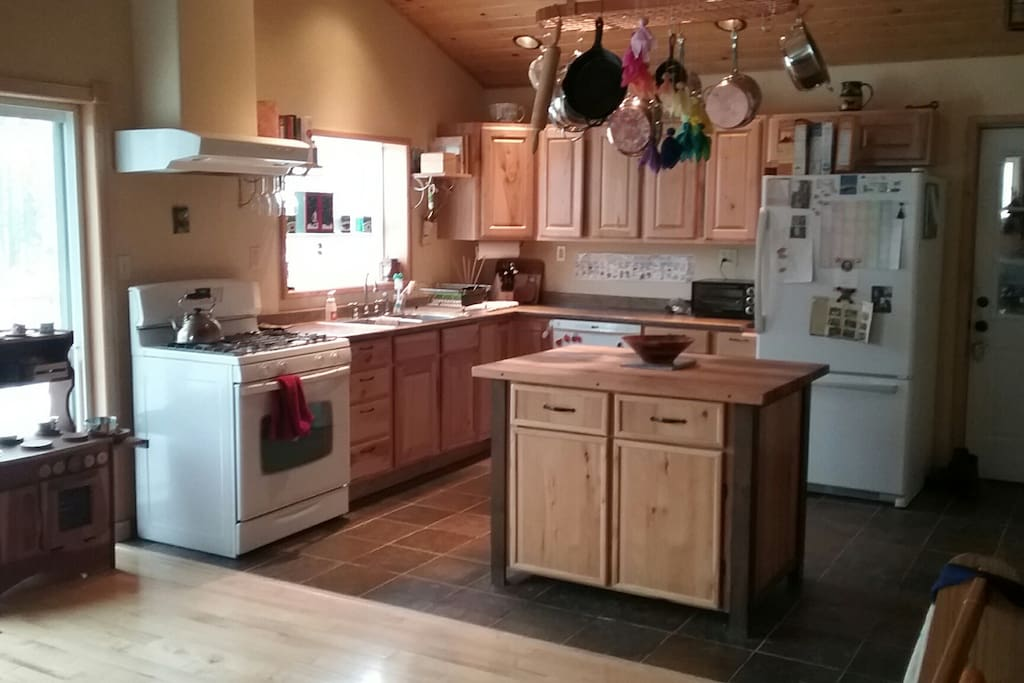 Full kitchen with gas stove, dishwasher and stainless steel cookware.
