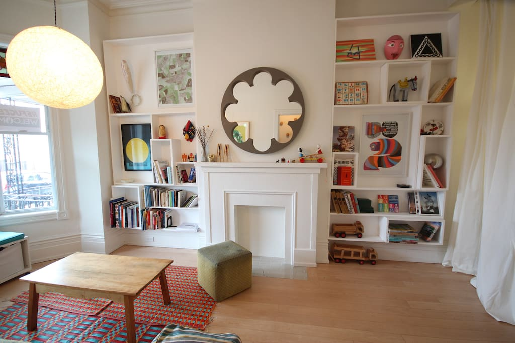 Living room display shelves filled with art & design books, prints, and other curios