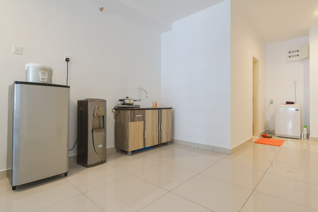 Simple kitchen area with fridge, induction cooker, jug kettle and rice cooker.