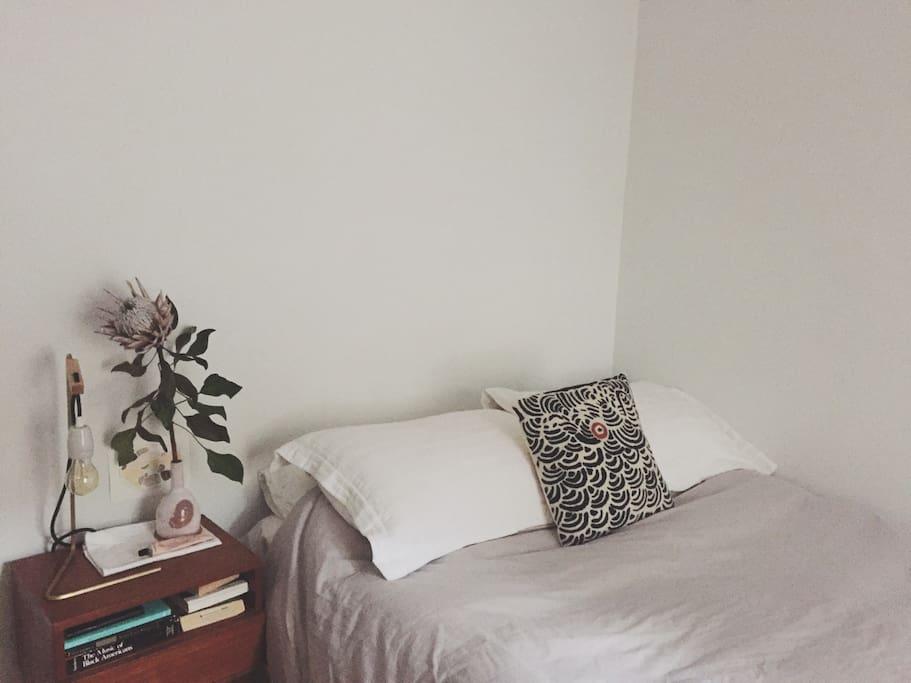 Beautiful bedroom, with bedside lamp designed by local furniture maker Felix Allen.