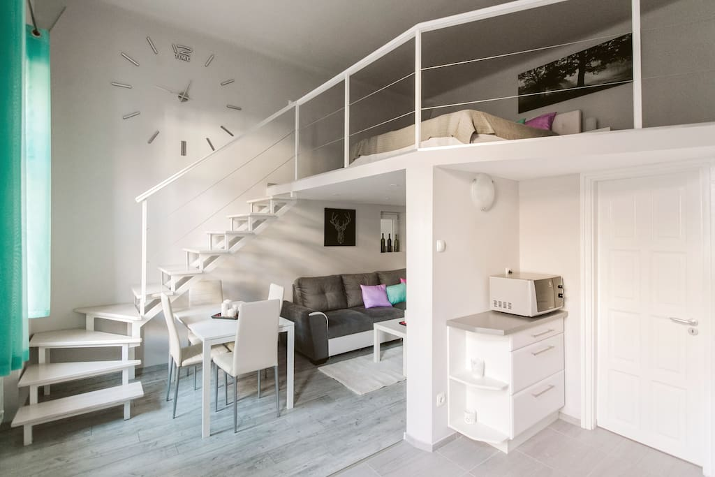 living room, dining area and mezzanine with the entrance to the bathroom from the kitchen