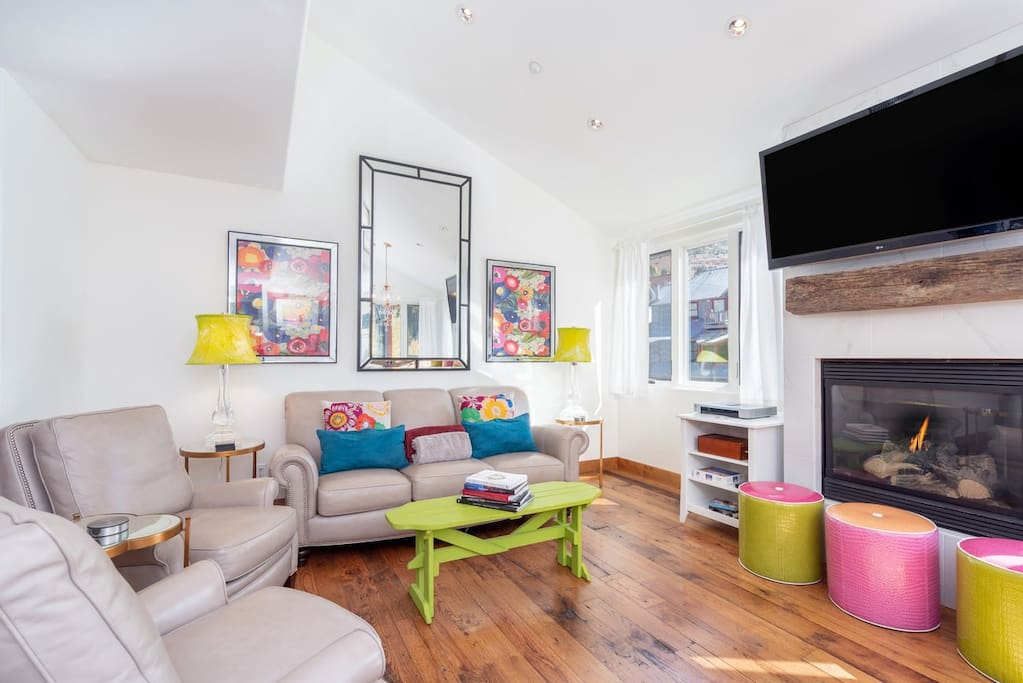 The living room is fun and bright, with a flat screen TV, a gas fire place, lounge and dining area.