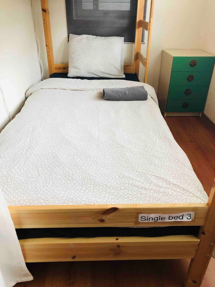 Single bed 3 is the lower bunker beds. The top part is not in use you can use it to put your things. Your bed is in the living room. You may share the apartment with 3 other person.