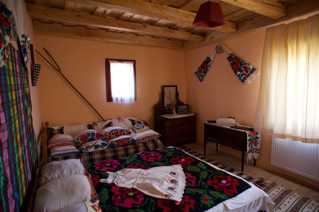 Large double room with hand embroidered linen, pillow cases, bed spread and petticoat. Natural-dye floor coverings are known as 'țoluri'.