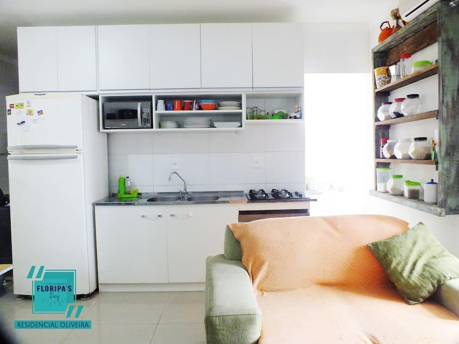 Cozinha com microondas, utensílios como prato, copo e talheres. Fogão com cooktop.