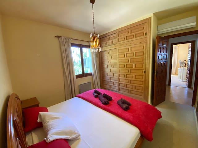 Dormitorio con cama de matrimonio. Aire condicionado de frío y calor y calefactor eléctrico. al abrir las ventanas o cerrar las persianas de madera durante el pico de calor del día (13-16h) hay una temperatura agradable en toda la casa.