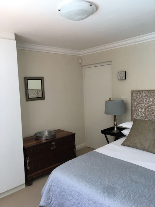 The main bedroom features a double wardrobe with hanging and shelf space, as well as a chest of three drawers.