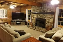 Living area with wood burning fireplace and TV.
