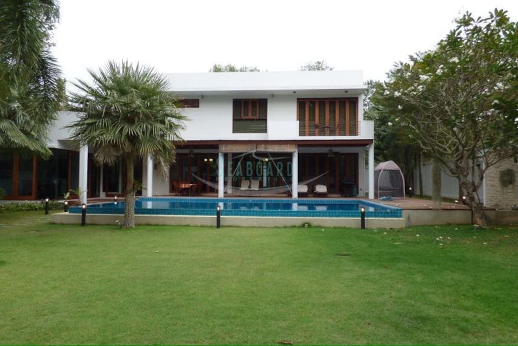 House frontage with large swimming pool and lawn surrounded by trees